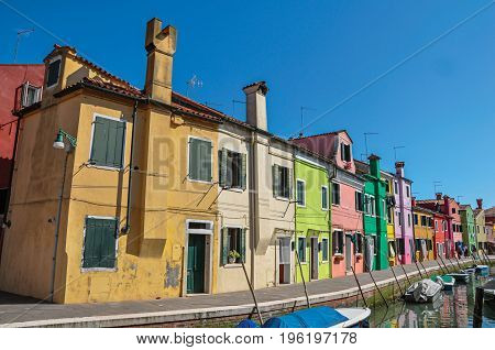 Panoramic view of colorful buildings, people and boats in front of a canal at Burano, a gracious little town full of canals, near Venice. Located in the Veneto region, northern Italy