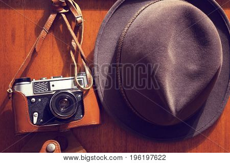 Old camera and hat.Retro style.Old stuff on the background of a wooden wall.
