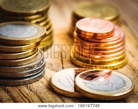 Stacked shiny white and golden Euro coins of different value on wood background finances investment stock savings concept warm toning close up