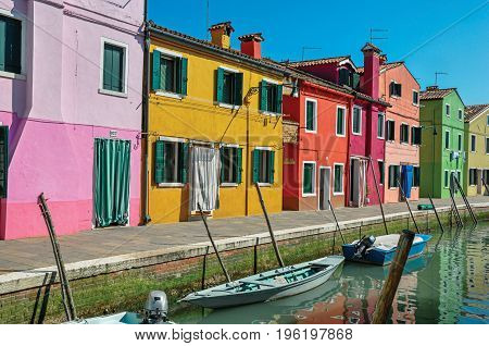 Burano, Italy - May 08, 2013. Panoramic view of colorful buildings and boats in front of a canal at Burano, a gracious little town full of canals, near Venice. In the Veneto region, northern Italy