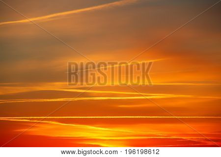 Clouds light in various warm colors with the sun below the horizon