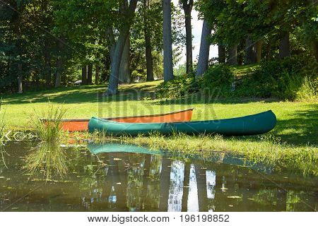 orange and green canoe in grass on river edge with water reflection
