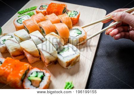 Sushi rolls and sauce and hand with chopsticks on black background. Traditional Japanese food.