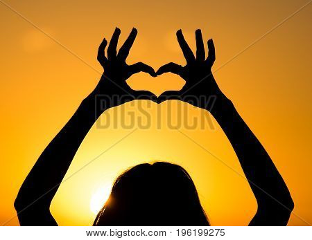 Silhouette of the heart by hands at sunset .