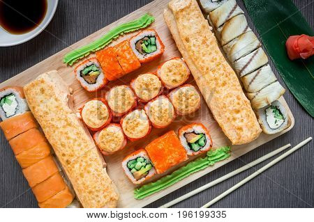 Japanese food. Sushi rolls and sauce with chopsticks on dark background. Top view. Flat lay