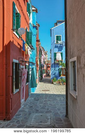 Overview of colorful terraced houses and clothes hanging in an alley on sunny day in Burano, a gracious little town full of canals, near Venice. Located in the Veneto region, northern Italy