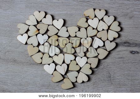 Heart shape from natural tree. Lovely heart shape by wooden small hearts on rustic wood table. Love theme concept with wooden hearts for Valentine's background and love theme.