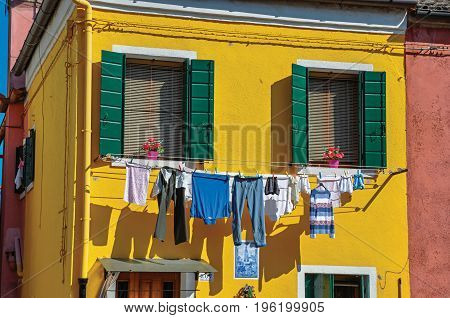 Burano, Italy - May 08, 2013. Close-up of windows on colorful walls and clothes hanging on sunny day in Burano, a gracious little town full of canals, near Venice. Veneto region, northern Italy
