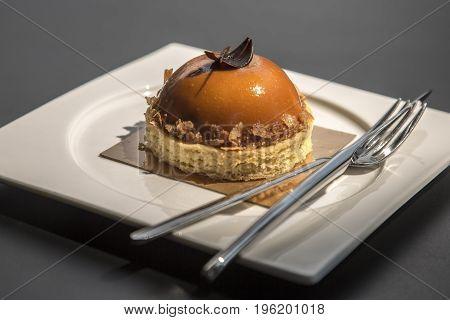 Caramel dessert with a chocolate slice on a dark table