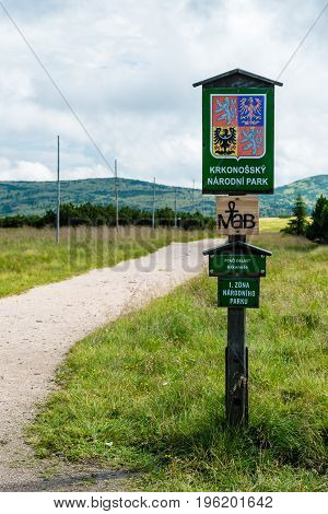 The wooden sign informs of Giant Mountains National Park (Krkonose). On a background is path leading to the Zlate navrsi faraway mountain trees and green grass. This is located near Labska bouda.
