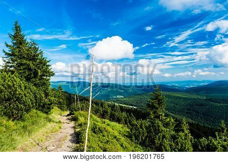 Path leading down from tableland Labska Louka in Giant Mountains (Krkonose). On background there are nice scenery with mountains hills trees forest and beautiful clear blue sky with clouds.