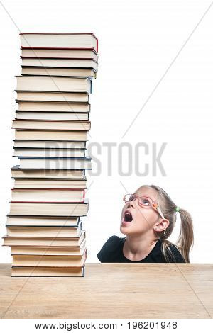 Little girl with glasses looks surprised at a high stack of books, standing on a table, isolated on a white background