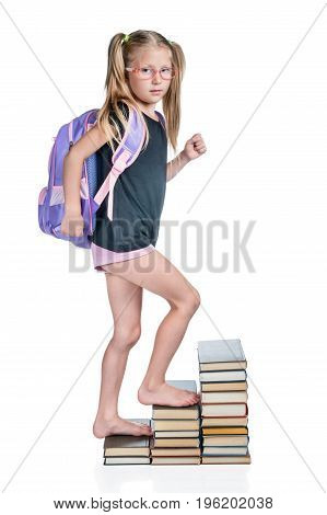 Schoolgirl with backpack walks up the stairs of books isolated on white background