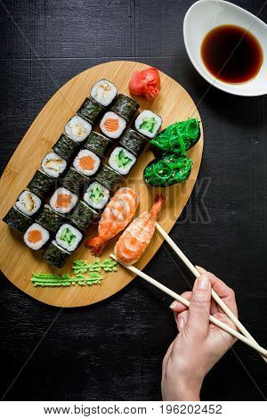 Sushi rolls and sauce and hand with chopsticks on a dark background. Japanese food. Top view. Flat lay