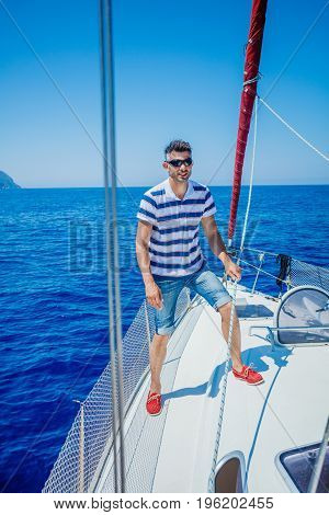 Young man sailing yacht. Sail vacation. People holidays travel