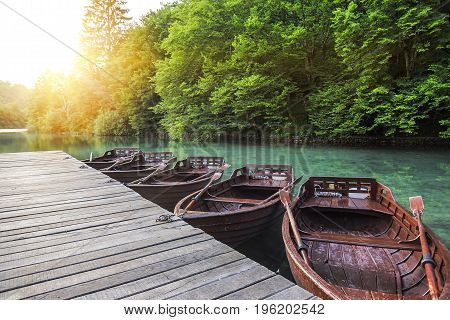 Wooden boats at the pier on the lake in the evening light. Plitvice Lakes, Croatia.
