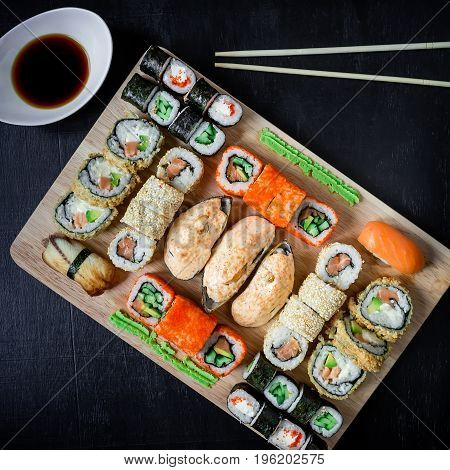 Japanese food - sushi rolls and sauce on a black background. Asian food background. Top view. Flat lay