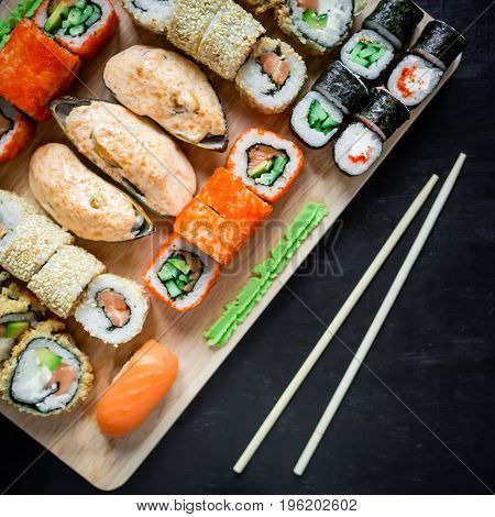 Japanese food - sushi rolls and sauce on a black wood background. Top view. Flat lay
