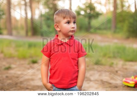 Happy child in a red T-shirt. Warm summer evening