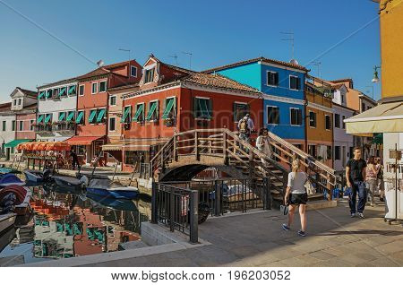Burano, Italy - May 08, 2013. View of colorful buildings, bridge and people in front of a canal at Burano, a gracious little town full of canals, near Venice. In the Veneto region, northern Italy