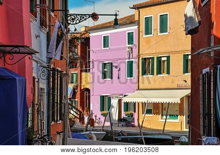 Burano, Italy - May 08, 2013. View of colorful buildings, people and boats in front of a canal at Burano, a gracious little town full of canals, near Venice. In the Veneto region, northern Italy