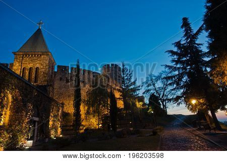 Cobblestone path along Kalemegdan fortress churches, towers and walls at blue hour in Belgrade, Serbia