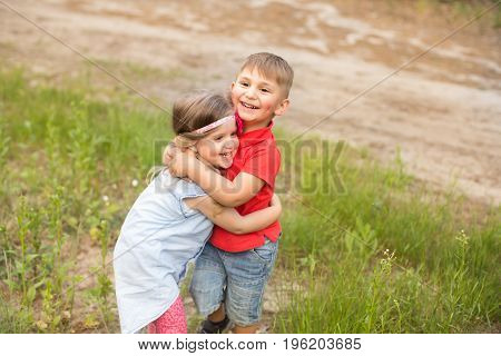 Happy boy and girl outdoors in summer park