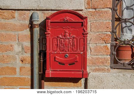 Close-up of a red post box stuck in a brick wall in the sunset at the city of Venice, the historic and amazing marine city. Located in the Veneto region, northern Italy