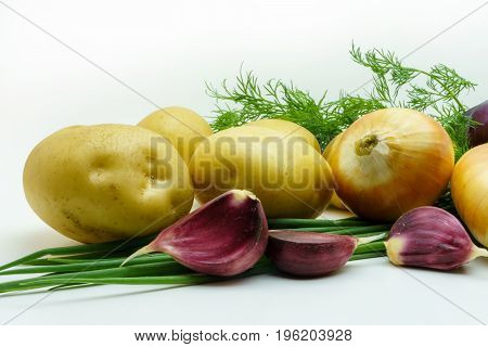 Assortment of fresh raw vegetables isolated on white background. Selection includes potato green onion garlic and dill