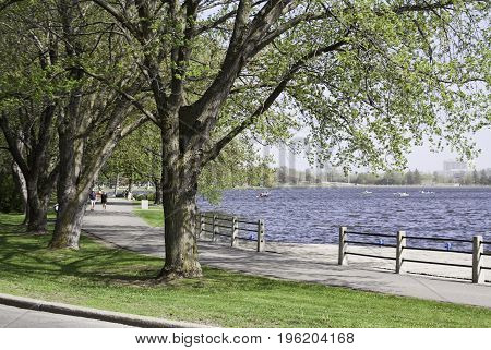 Ottawa, Ontario, May 18, 2017 -- Wide landscape of people on a walking path along the Rideau Canal with trees and buildings in the background on a bright sunny day in May at the International Tulip Festival in Ottawa, Ontario.