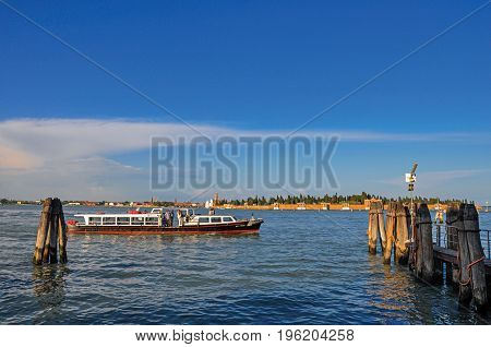 Venice, Italy - May 08, 2013. Panoramic view of Venice lagoon with pier and boat at the sunset in the city of Venice, the historic and amazing marine city. Located in the Veneto region, northern Italy