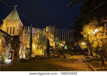Cobblestone path along Kalemegdan fortress churches, towers and walls at night in Belgrade, Serbia
