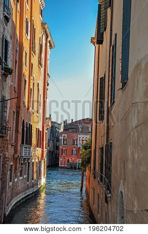 Panoramic view of buildings on a canal that ends on another canal at the sunset, in the city center of Venice, the historic and amazing marine city. Located in the Veneto region, northern Italy
