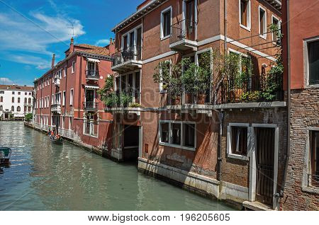 Venice, Italy - May 09, 2013. View of buildings in front of the canal with gondola in the background, at the city center of Venice, the historic and amazing marine city. Veneto region, northern Italy
