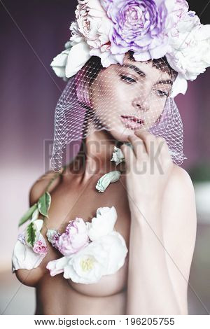 Portrait of a beautiful sensual girl with pink hair and flowers