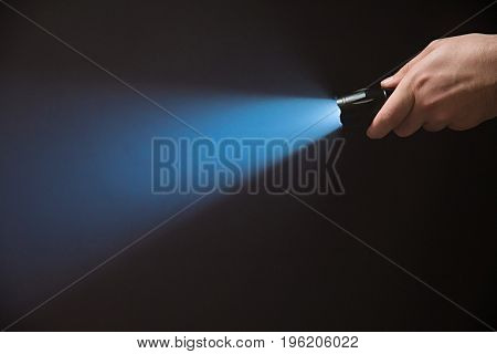Male Hand Holding A Led Flashlight With A Narrow Blue Beam On A Black Background, Leaving The Right