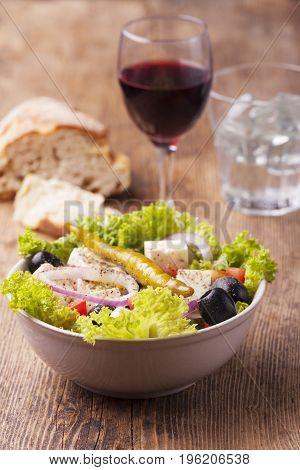 fresh greek salad with olives on wood