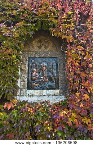 Detail from a church wall, Virgin Mary with Jesus Christ surrounded with autumn leaves at Kalemegdan, Belgrade, Serbia