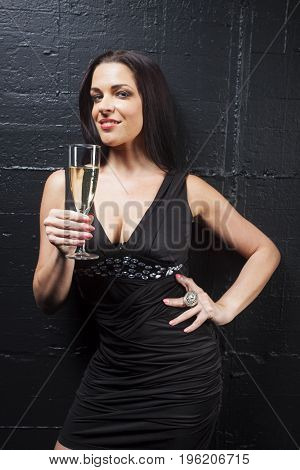 smiling woman with a glass of  champagne on black