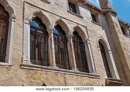 Close-up of windows with columns and arches in typical Venetian style in ancient building. At the city center of Venice, the historic and amazing marine city. Located in Veneto region, northern Italy