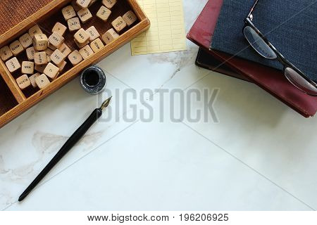 Above view styled desktop with vintage school supplies, word blocks and white marble copy space.