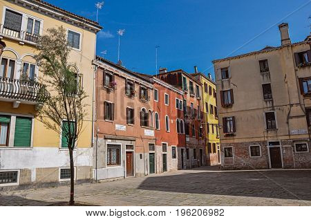Venice, Italy - May 09, 2013. View of old colorful buildings in an alley and square with blue sunny sky. City center of Venice, the historic and amazing marine city. Veneto region, northern Italy