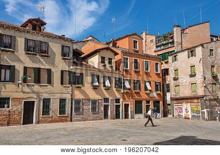Venice, Italy - May 09, 2013. View of old colorful buildings and pedestrian in a square with blue sunny sky. City center of Venice, the historic and amazing marine city. Veneto region, northern Italy