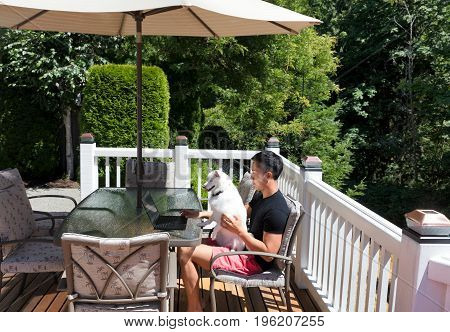 Young man and his pet dog working from home on outdoor deck