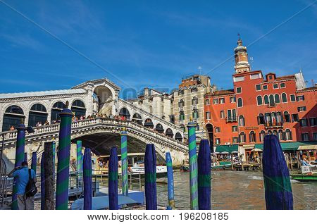 Venice, Italy - May 09, 2013. View of colorful buildings, gondolas and the Rialto Bridge with people. At the city center of Venice, the historic and amazing marine city. Veneto region, northern Italy