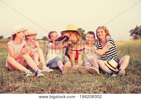 Four children and one adul female sitting with a dog outdoors on a grass at summer sunny field