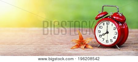 Summer time concept - website banner of a red alarm clock and orange lily flower