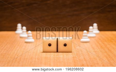 A domino dice and chess pawns on a wooden background the most popular board games around the world