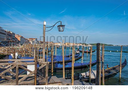 Venice, Italy - May 09, 2013. Panoramic view of Venice lagoon with pier and gondolas with blue sunny sky and lamp At the city of Venice, the historic and amazing marine city. Veneto region