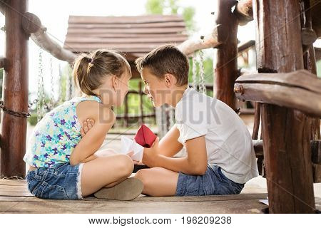Happy two caucasian siblings sittign in a wooden house outdoors on summer day holding a paper boats in their hands sharing a secret